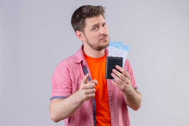 Молодой красивый путешественник мужчина держит билеты на самолет, указывая пальцем в камеру с подозрительным выражением лица, стоящего над белой стеной