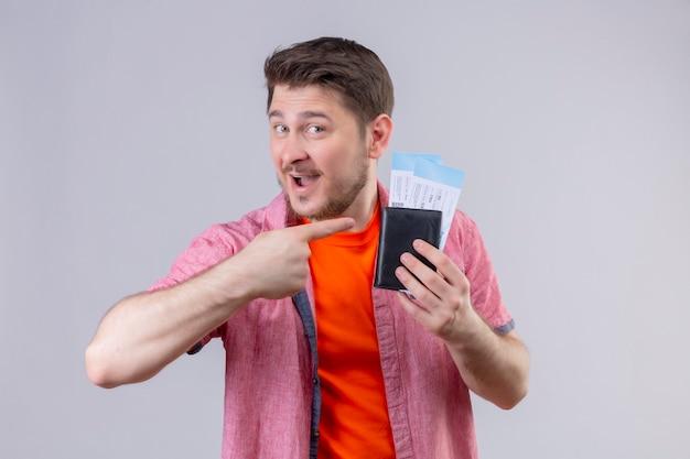 Молодой красивый путешественник мужчина держит билеты на самолет, указывая пальцем на них, весело улыбаясь и счастливо улыбаясь, стоя над белой стеной