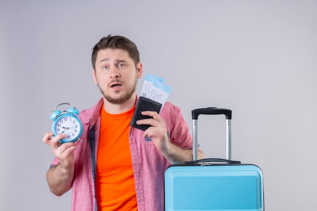 Young handsome traveler man holding blue suitcase and airplane tickets with alarm clock confused and disappointed standing over white wall