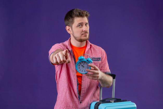 Uomo giovane viaggiatore bello che tiene la valigia blu e sveglia che indica con il dito