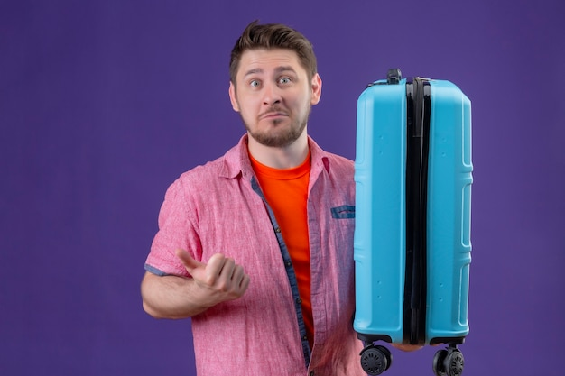 Young handsome traveler man holding blue suitcase pointing to the side