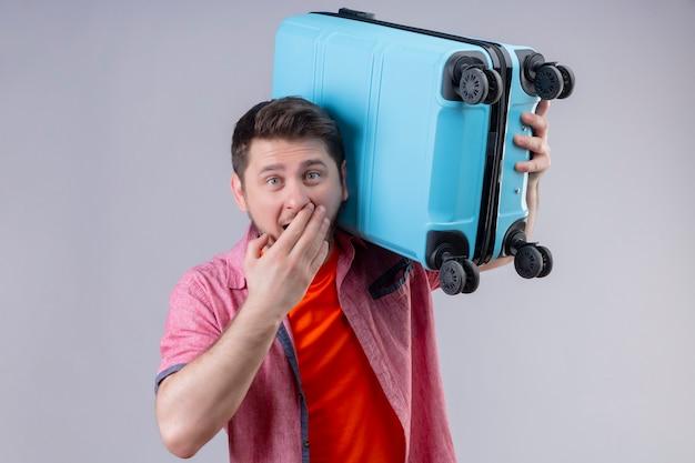 青いスーツケースを持って若いハンサムな旅行者男は驚いて、白い壁の上に立って手で驚いて覆っている口