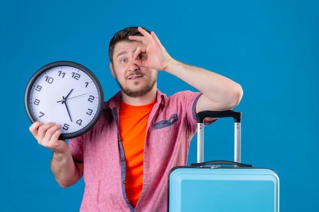 Uomo giovane viaggiatore bello che tiene orologio e valigia sorridente positivo