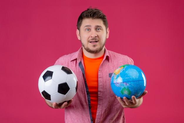 Молодой красивый путешественник мужчина держит футбольный мяч и глобус с запутанным выражением лица