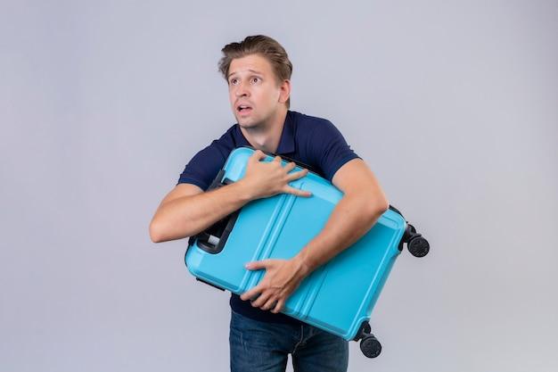 Молодой красивый путешественник мужчина держит чемодан, опаздывает, глядя вверх с выражением страха, стоя на белом фоне