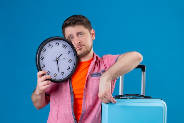 Young handsome traveler man holding suitcase and clock with sad expression