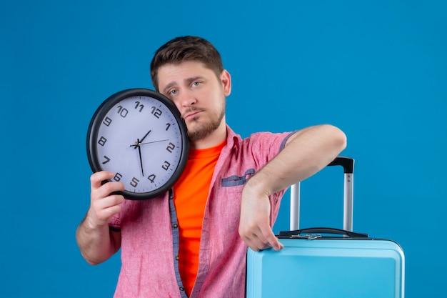 Uomo giovane viaggiatore bello che tiene la valigia e l'orologio con l'espressione triste