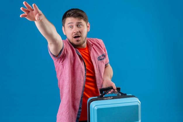 青い壁にスーツケースを感情的で心配して身振りで示す立っている若いハンサムな旅行者男