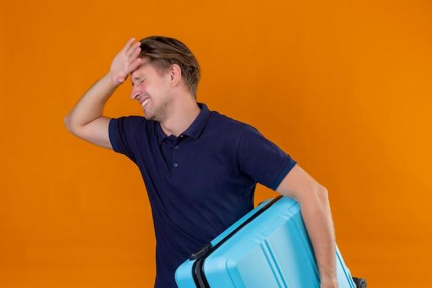 オレンジ色の背景上の間違いのための頭の上の手で退屈と疲れて立っている探しているスーツケースを持って若いハンサムな旅行者男