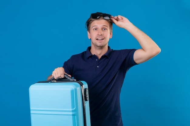 Молодой красивый путешественник мужчина держит чемодан, выглядящий возбужденным и счастливым, готовым к путешествию, стоя на синем фоне