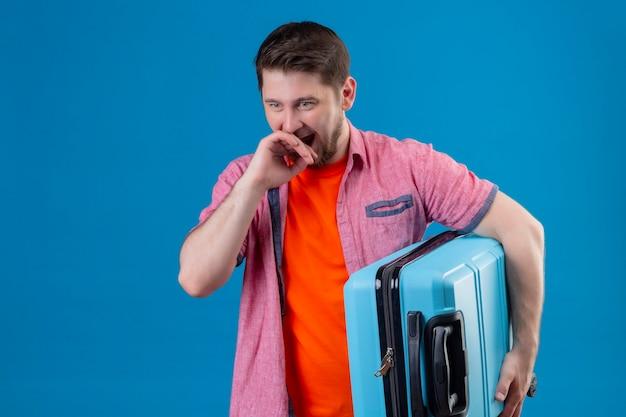 青い壁を越えて立っている手で驚いて、驚いて覆っている口を探しているスーツケースを持って若いハンサムな旅行者男