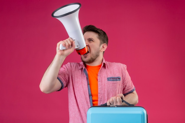 Young handsome traveler man holding suitcase and megaphone shouting to it
