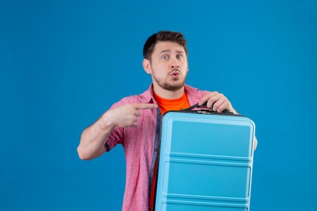 青い壁の上に立っている顔に困惑した表情で側に指で指しているスーツケースを持って若いハンサムな旅行者男