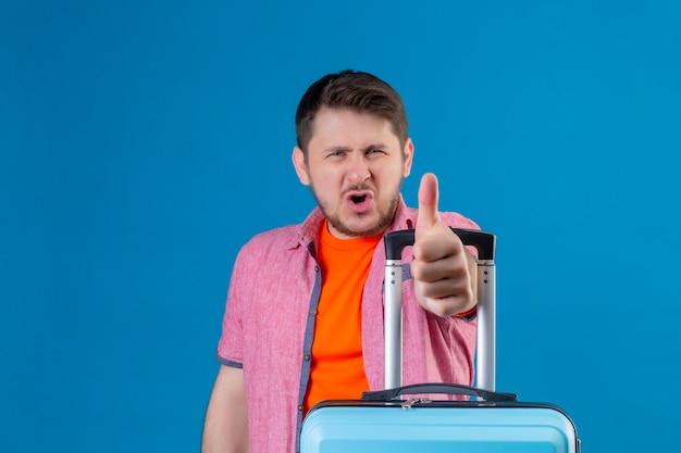 非常に終了し、青い壁に幸せな立っている親指を示すスーツケースを持って若いハンサムな旅行者男
