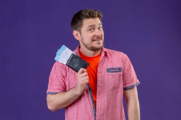 Молодой красивый путешественник мужчина держит билеты, улыбаясь