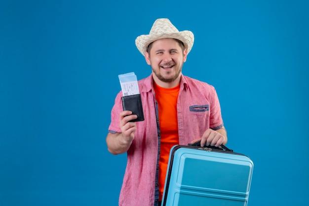 Молодой красивый путешественник в летней шляпе держит чемодан и билеты на самолет, выглядит уверенно и счастливо улыбается, весело стоя у синей стены