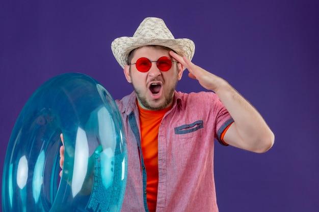 頭の上の手でインフレータブルリング付き夏帽子の若いハンサムな旅行者男