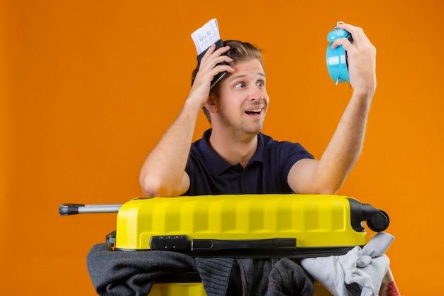 Молодой красивый путешественник, стоящий с чемоданом, полным одежды, держит будильник и авиабилеты, глядя на будильник, удивлен и обеспокоен на оранжевом фоне