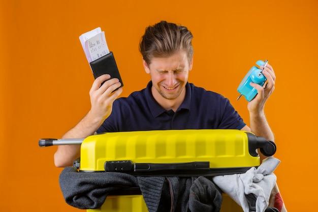 Молодой красивый путешественник, стоящий с чемоданом, полным одежды, держит будильник и авиабилеты с закрытыми глазами, несчастный плачет на оранжевом фоне