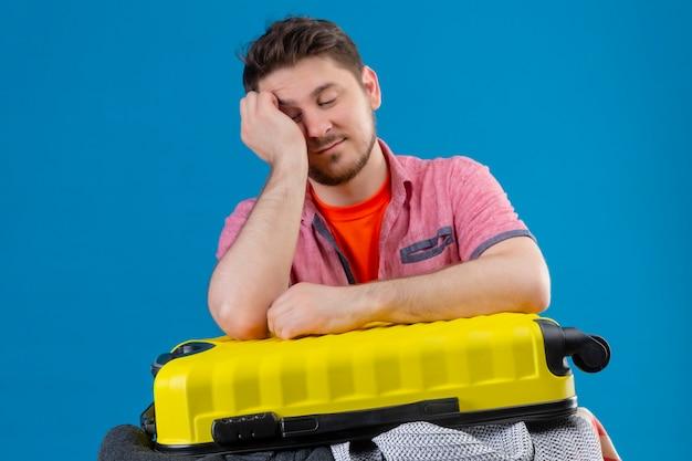 若いハンサムな旅行者の男の服の完全なスーツケースの側に立って、疲れて
