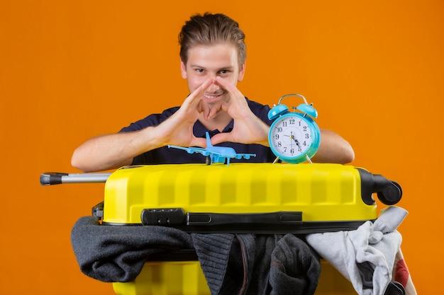 目覚まし時計とおもちゃの飛行機の服でいっぱいのスーツケースを持って立っている若いハンサムな旅行者の男オレンジ色の背景に肯定的で幸せな笑顔を見て手でハートのジェスチャーを作る