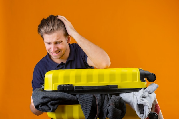 オレンジ色の背景上の間違いのための頭の上の手で服でいっぱいのスーツケースを持って立っている若いハンサムな旅行者男