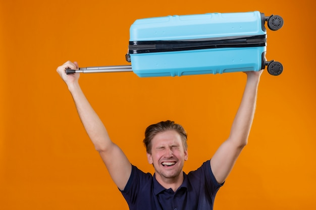 Young handsome traveler man standing with suitcase over his head with closed eyes excited and happy over orange background