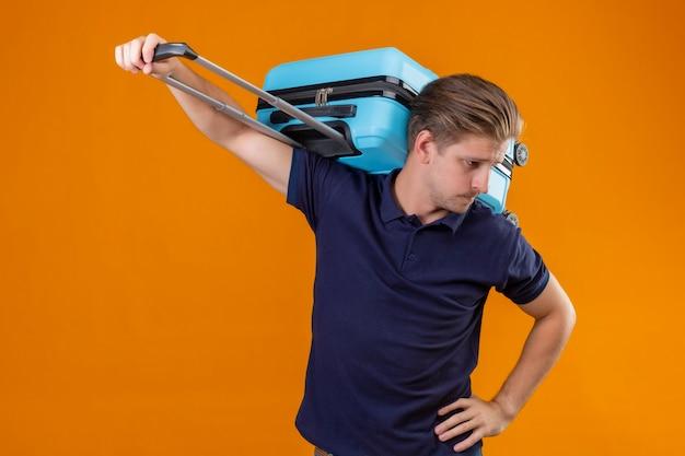スーツケースを持って立っている若いハンサムな旅行者男はさておき、オレンジ色の背景に疲れて退屈