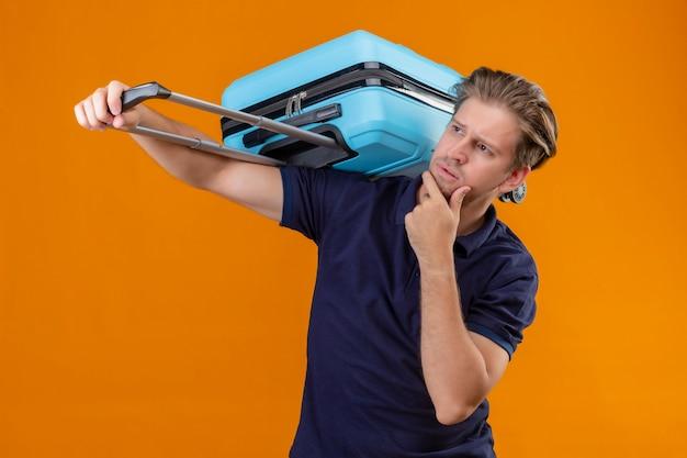 オレンジ色の背景に疑問を持つあごの思考に手でスーツケースをよそ見で立っている若いハンサムな旅行者男