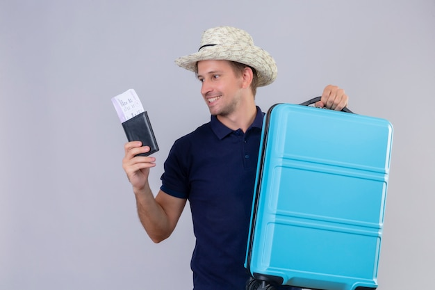 Young handsome traveler man in summer hat standing with suitcase holding air tickets looking aside with happy face smiling cheerfully over white background