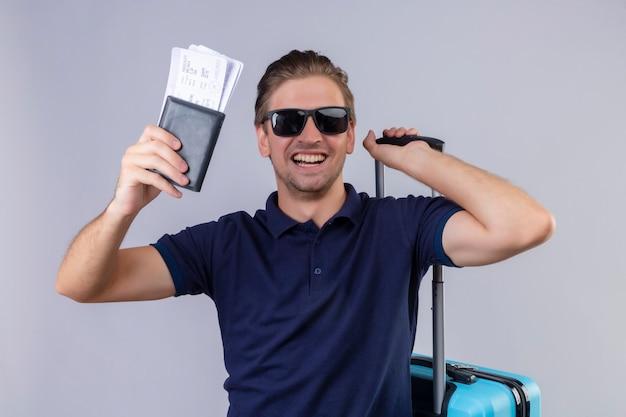 가방 행복 서 항공 티켓을 들고 검은 선글라스를 착용하는 젊은 잘 생긴 여행자 남자는 흰색 배경 위에 유쾌하게 웃고 종료