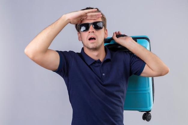 Uomo giovane viaggiatore bello che indossa occhiali da sole neri che tengono la valigia guardando lontano con la mano per guardare qualcosa in piedi su sfondo bianco