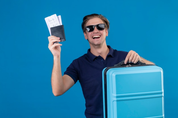 파란색 배경 위에 유쾌하게 웃는 행복한 얼굴로 카메라를보고 항공 티켓을 들고 가방으로 서 검은 선글라스를 착용하는 젊은 잘 생긴 여행자 남자