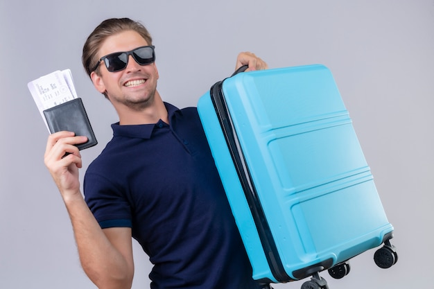 Young handsome traveler man wearing black sunglasses standing with suitcase holding air tickets looking at camera with happy face smiling cheerfully over white background