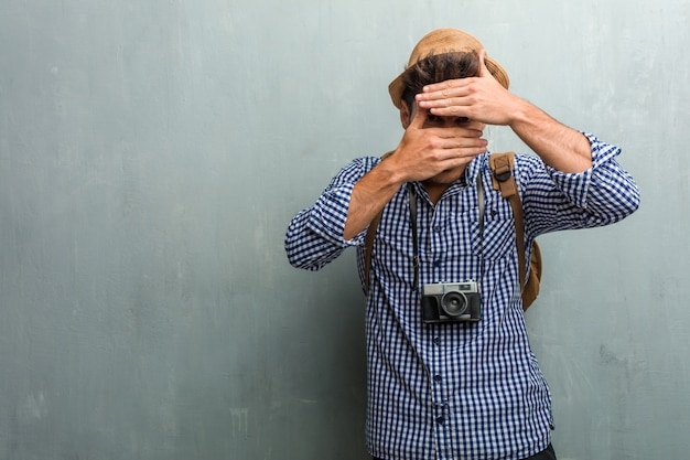 Young handsome traveler man wearing a straw hat, a backpack and a photo camera looking through a gap, hiding and squinting