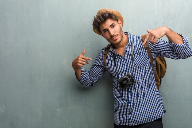 Young handsome traveler man wearing a straw hat, a backpack and a photo camera proud and confident, pointing fingers, example to follow, concept of satisfaction, arrogance and health