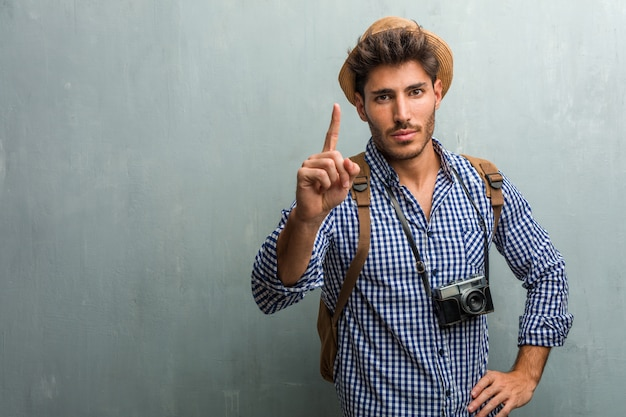 Young handsome traveler man wearing a straw hat, a backpack and a photo camera showing num