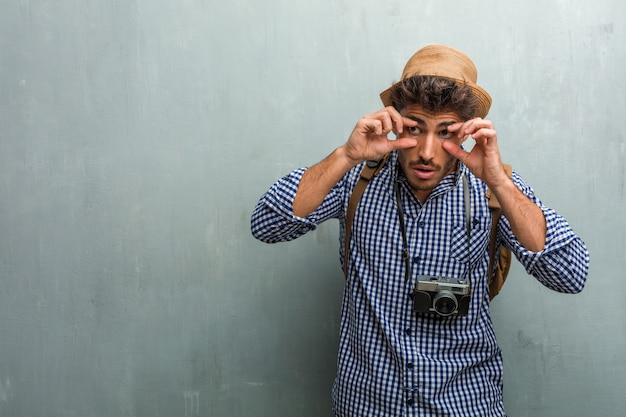 Young handsome traveler man wearing a straw hat, a backpack and a photo camera surprised and shocked