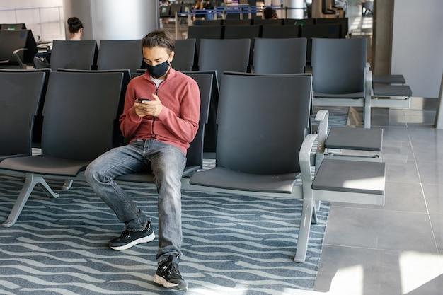 Young handsome traveller in a mask in lounge of airport terminal using smartphone app in public wifi area, messaging