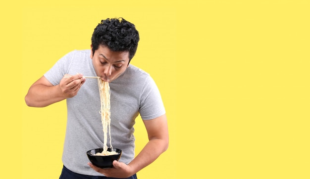 Young handsome trendy asian man eating yummy hot and spicy instant noodle using chopsticks and bowl