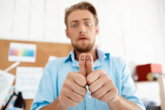 Giovane uomo d'affari bello turbato che mostra i pollici su con i disegni dei fronti divertenti. concentrarsi sulle mani. interno di ufficio moderno bianco