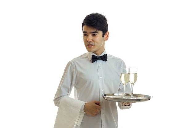 샴페인 잔과 쟁반을 들고 흰 셔츠에 젊은 잘 생긴 웨이터는 흰 벽에 격리됩니다