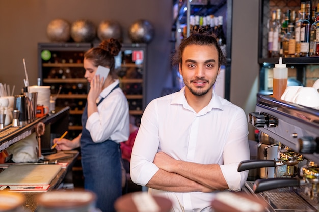 Young handsome waiter in white shirt crossing arms by chest while standing by coffee machine on background of colleague phoning