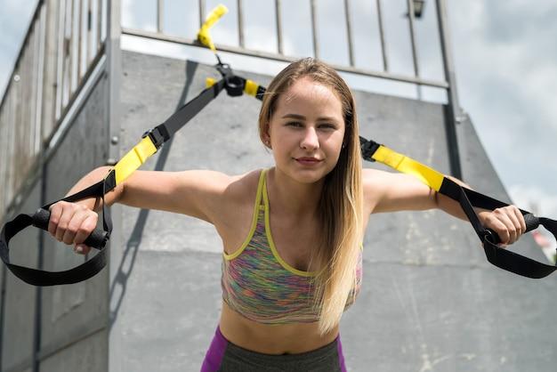 自然の中でtrxフィットネスストラップで腕立て伏せトレーニングアームをやっているスポーツウェアの若いハンサムな女性。健康的な生活様式