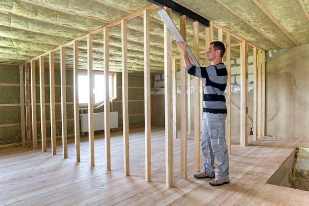 Young handsome worker constructing wooden frame for future walls in big light mansard room with oak floor, insulated with rock wool ceiling and low attic window. construction and renovation concept.