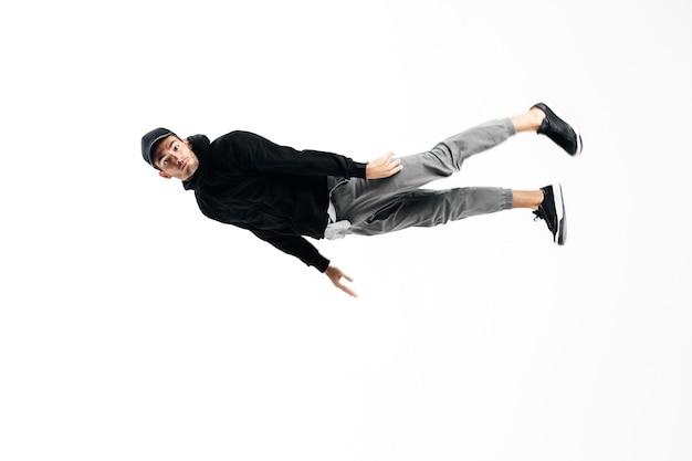 若いハンサムな若いダンサーはブレイクダンスを踊っています。彼は踊りながら宙に浮く