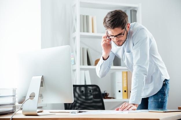 Молодой handsoome деловой человек, стоящий за столом, работая над документами с мобильным телефоном в офисе