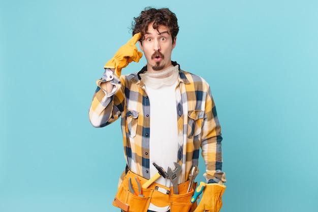 Молодой разнорабочий домработник выглядит удивленным, осознавая новую мысль, идею или концепцию
