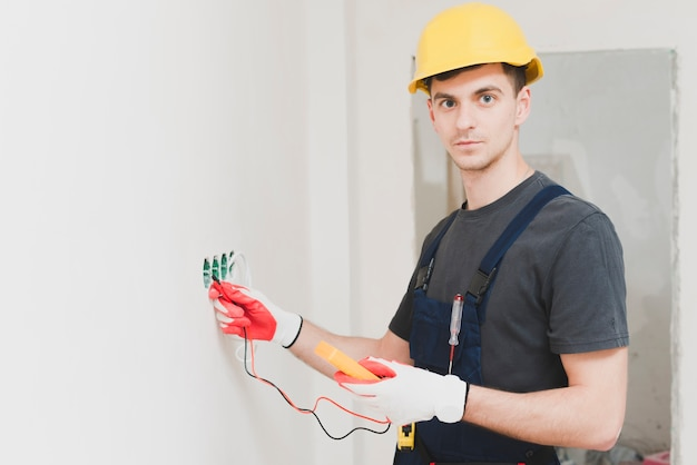 Young handyman measuring voltage