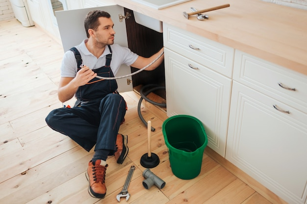 Young handyman sit on floor in kitchen